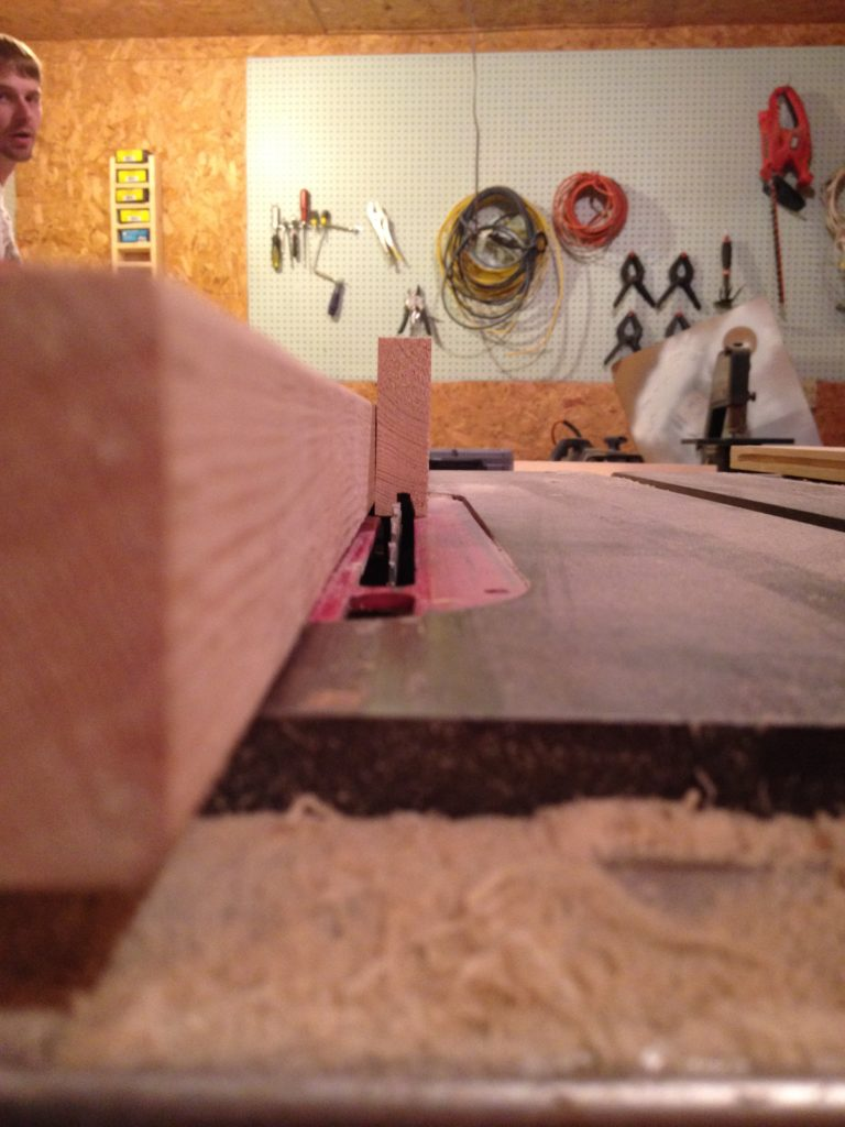 Rip fence on table saw set to ¼ inch from the blade to cut dadoes into cabinet door frame