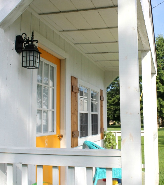 Shutters on front porch of she shed building--wooden shutters hung on each side of front window