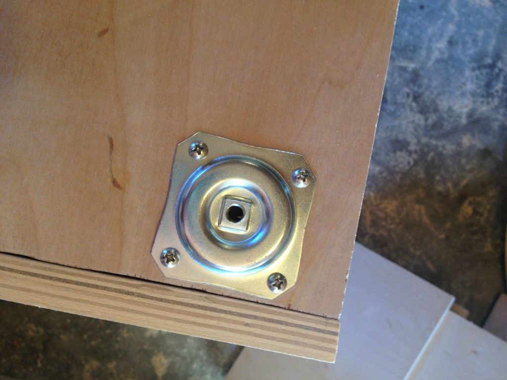 Furniture feet attachment plate mounted on bottom of cabinet