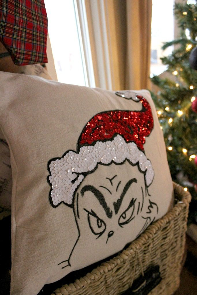 Close up of DIY Grinch Pillow Cover in basket by Christmas Tree
