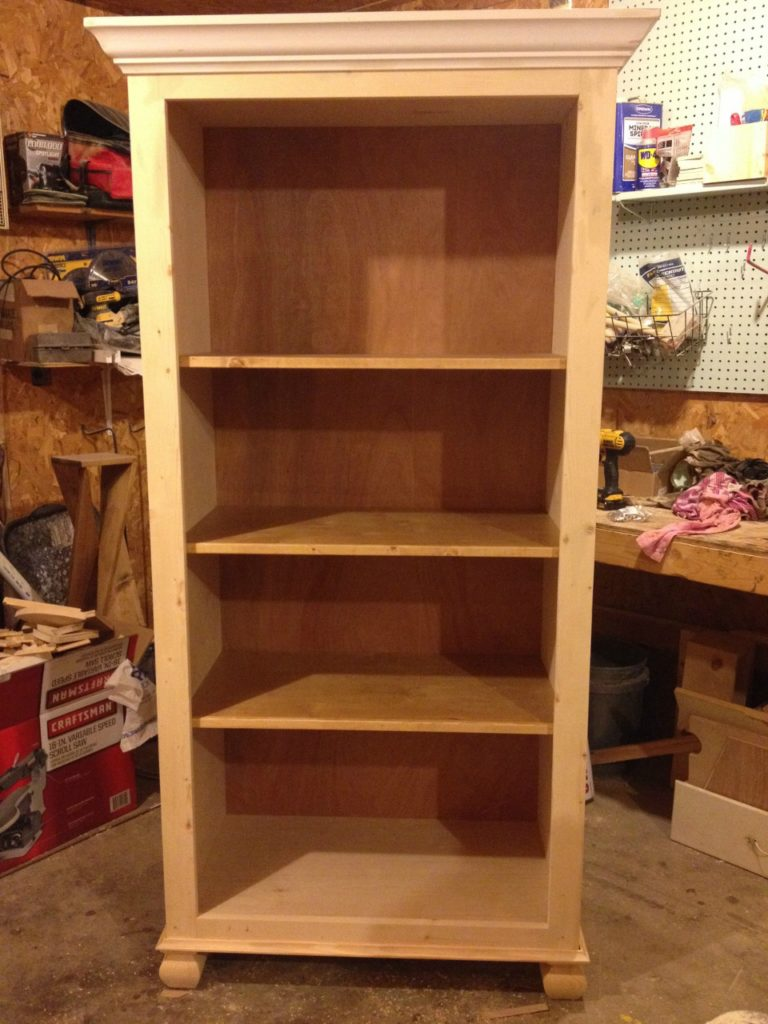 Unfinished stand alone tall bookshelf in workshop