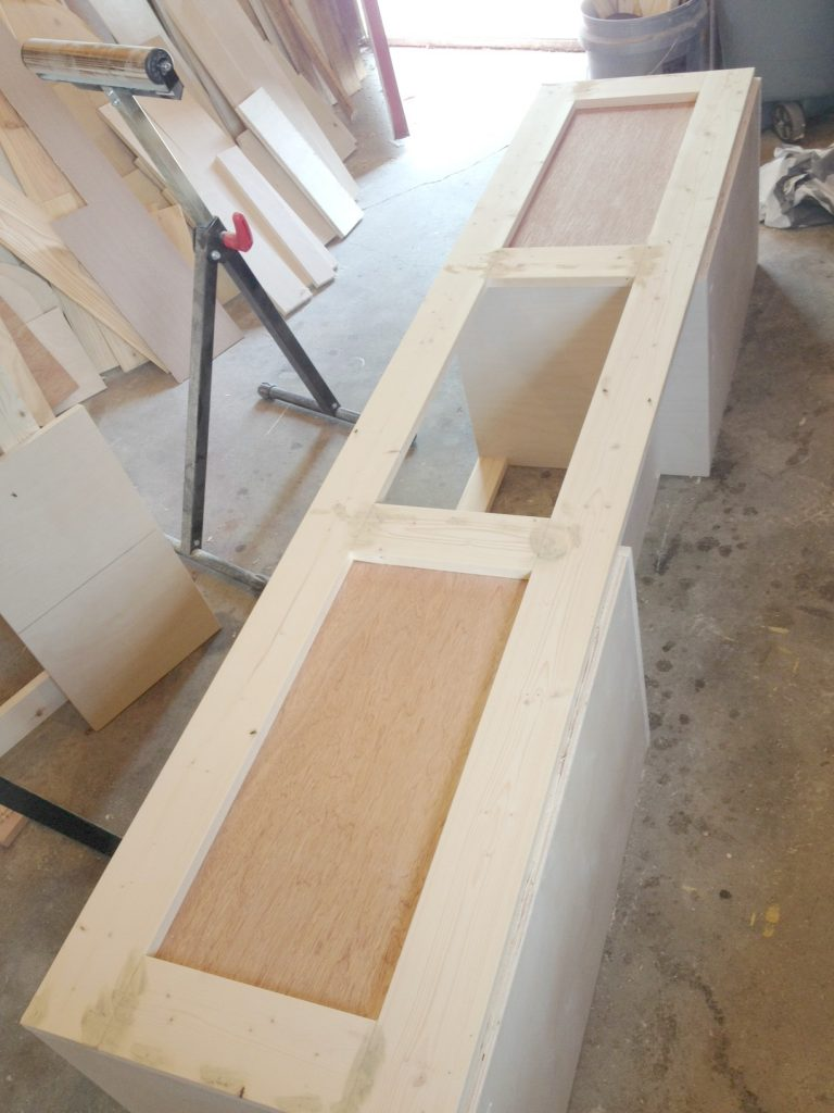 Plywood panels added to shoe bench to attach chevron pattern
