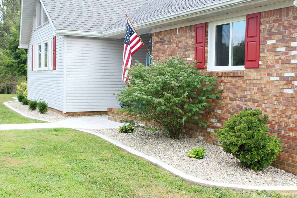 Indiana river rock and concrete edging update this home's worn out landscape