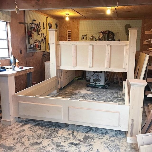 Unfinished DIY storage bed in small woodworking shop