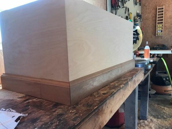 Mitered baseboard along bottom of storage trunk box