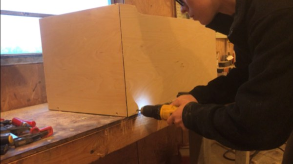 Screwing bottom panel of storage chest in place