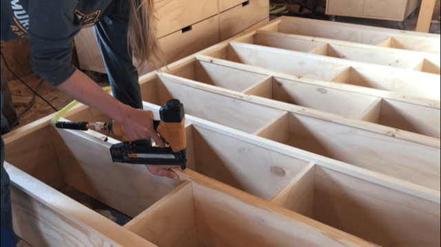 Nail front edge trim onto DIY modern stand alone bookshelf