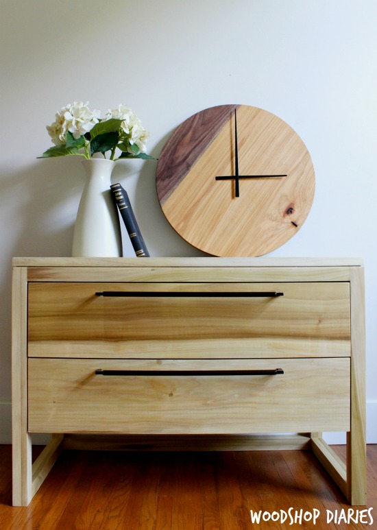 Two tone DIY wood clock sitting on modern two drawer nightstand with vase and book