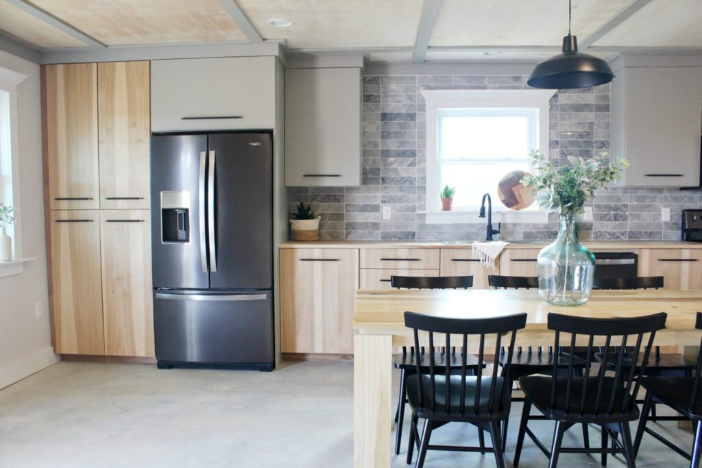 Modern wood and grey kitchen with backsplash tile and black stainless refrigetator