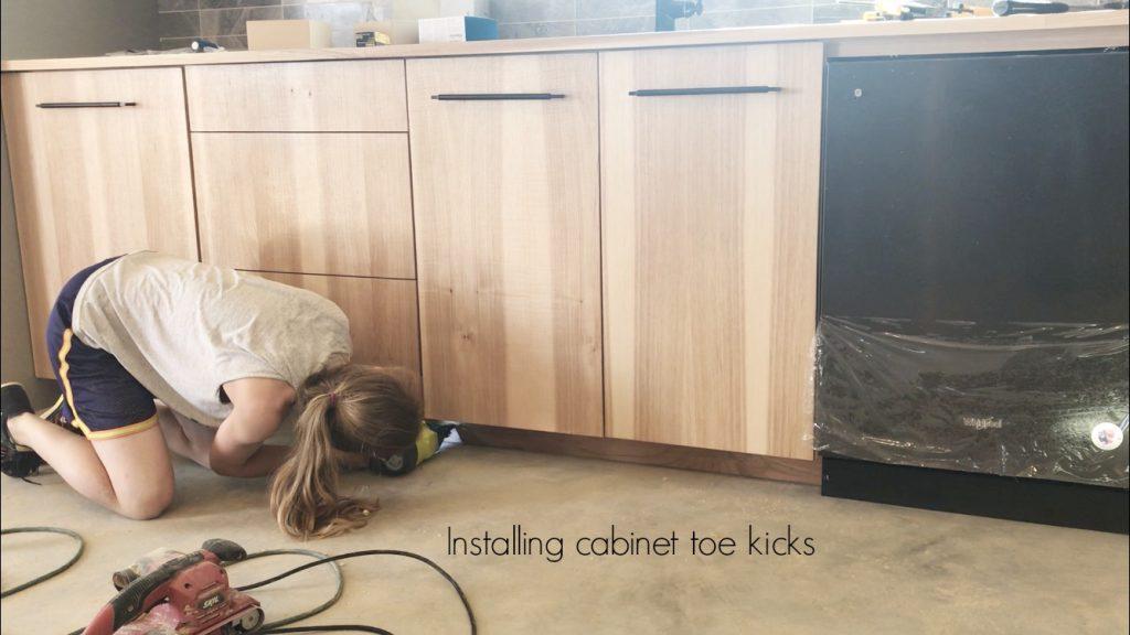 Shara Woodshop Diaries nailing toe kicks onto base cabinets