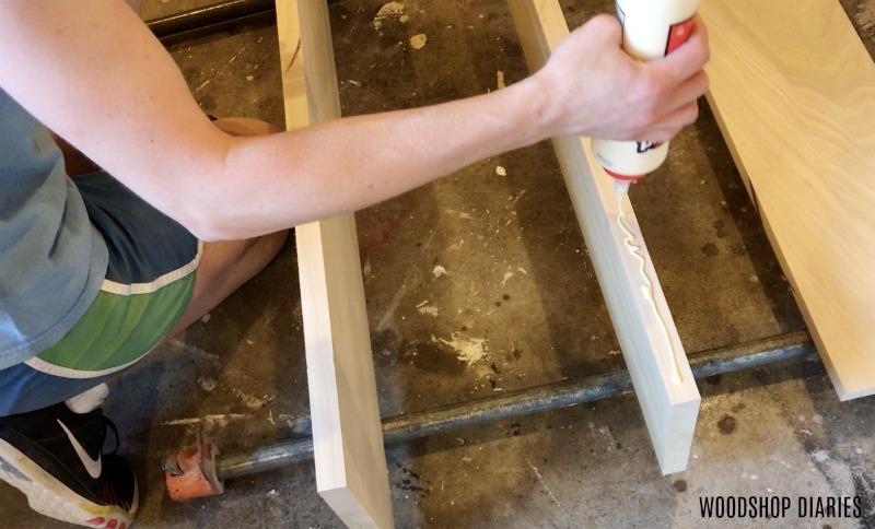 apply glue to headboard panel on DIY modern bed frame