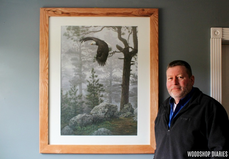 Dad next to his custom DIY picture frame with eagle print in his blue office