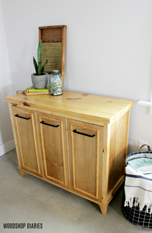Finished DIY tilt out laundry hamper cabinet stained with summer oak