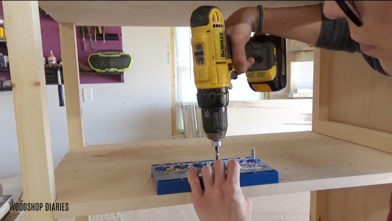 Using drill and Kreg shelf pin jig to drill out adjustable shelf pin holes in laundry cabinet