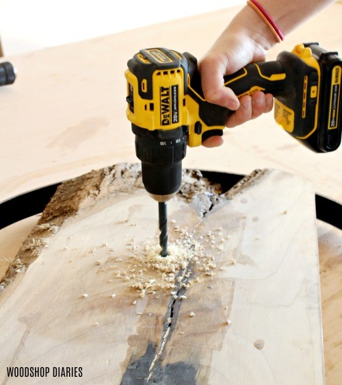 Using drill to drill a hole into wood