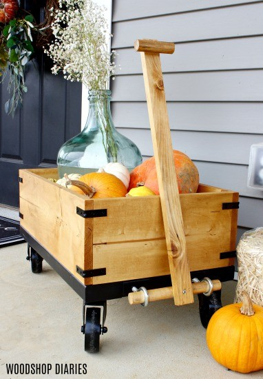 Simple wood and black accent DIY fall wooden wagon decorated with pumpkins and hay bale by front door