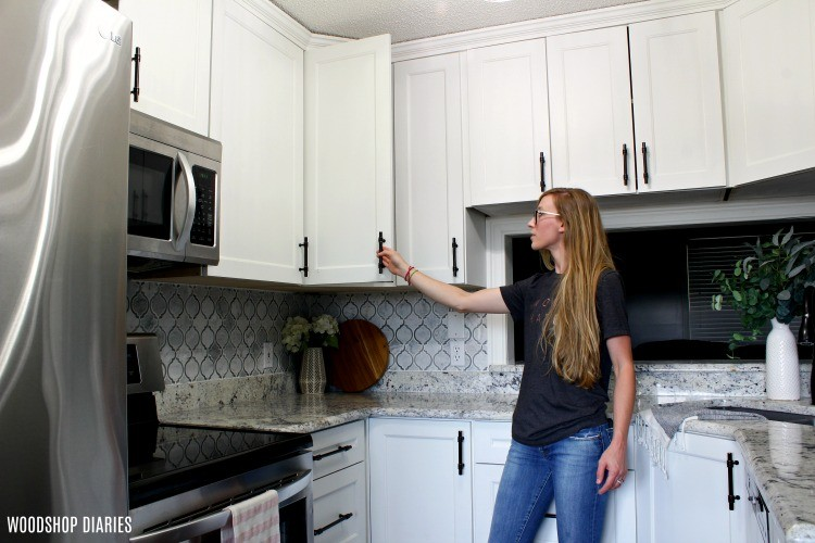 Shara Woodshop Diaries in Sister's kitchen opening cabinet doors