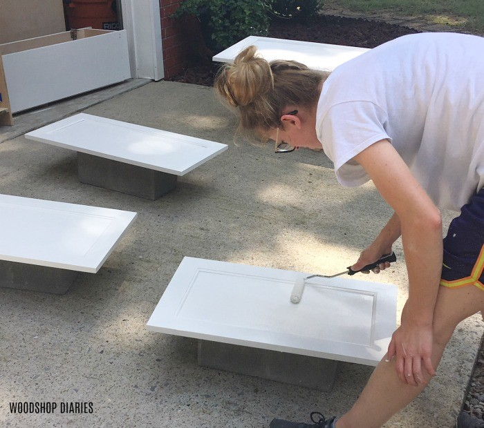 Shara rolling primer onto cabinet doors--diy furniture tips--prime before painting raw wood