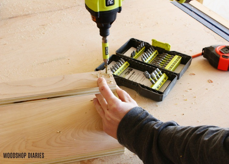 Using a driver to drive a screw into a plywood rack