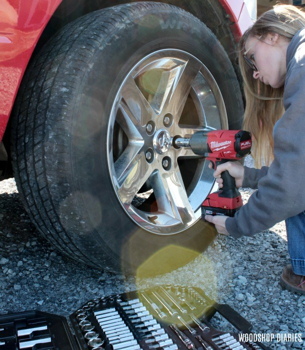 Shara using impact wrench to loosen lug nuts on truck wheel
