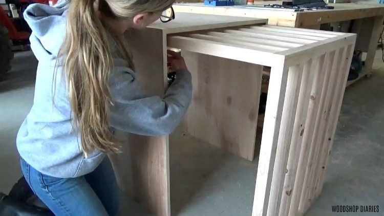 Shara marking where to install drawer slides on underside of top of sliding door