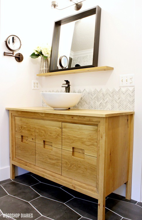 Floating shelf with black framed mirror over modern white oak vanity in modern bathroom remodel