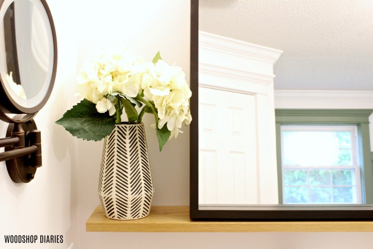 Close up of floating mirror shelf corner with vase and flowers on shelf