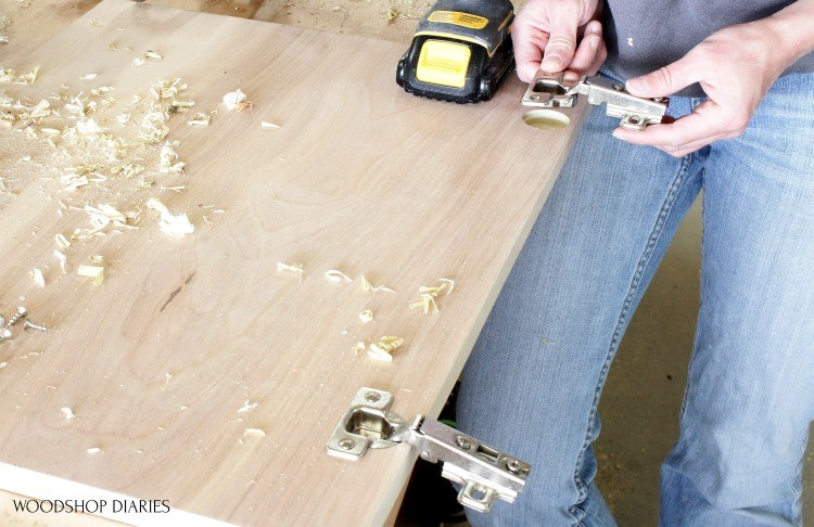 Placing hinge into hole drilled for concealed hinge on cabinet door