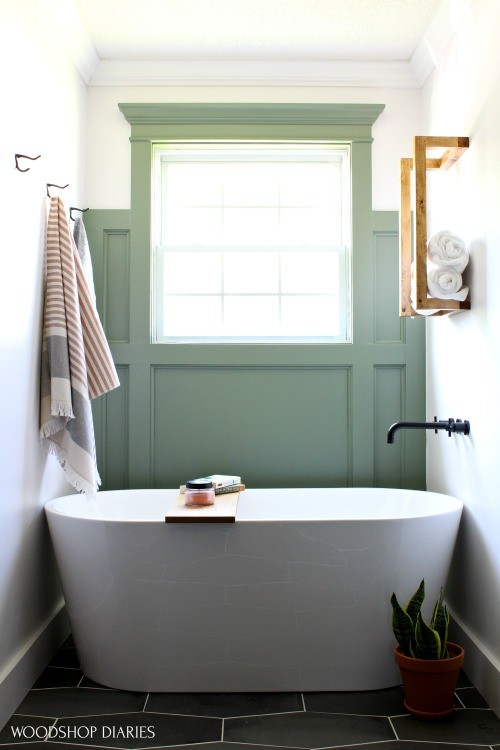 Freestanding tub in bathroom nook with scrap wood towel rack hanging above it with towels stacked