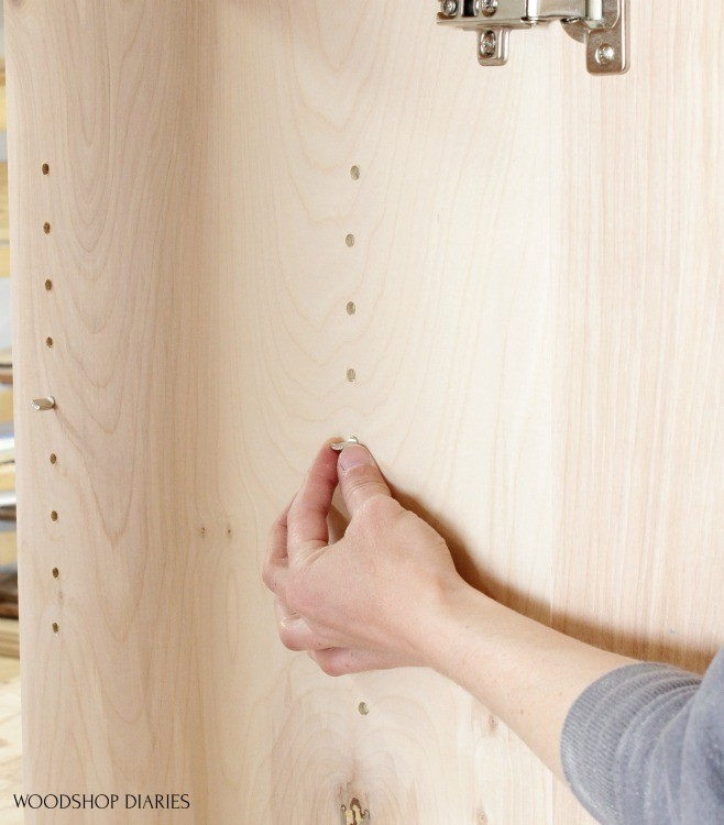 Installing shelf pins in shelf pin holes in cabinet carcass