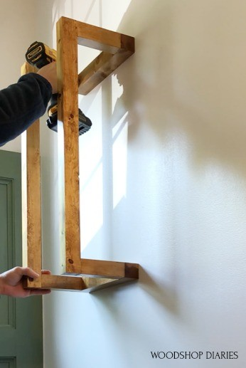 """Shara attaching towel rack to wall using driver and 3"""" wood screws"""