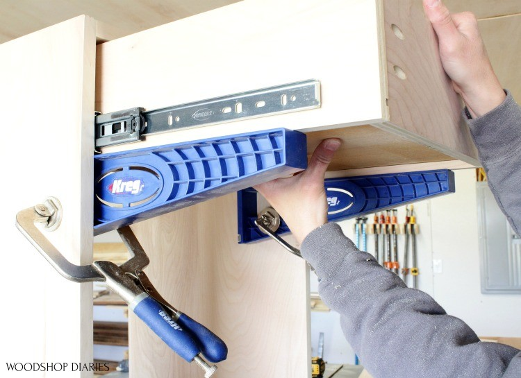 Installing drawer box into cabinet on top of drawer slide jigs clamped to cabinet carcass