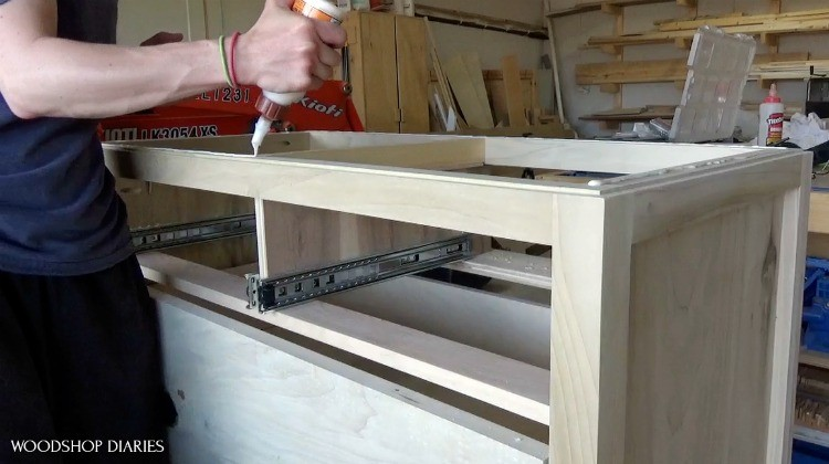 Shara applying wood glue to top of dresser frame