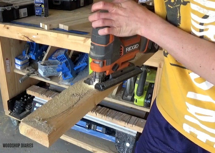 Using a jig saw to cut pergola design shape into top boards of decorative garden bed trellis