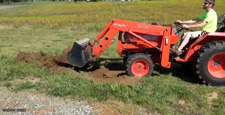 Danny moving dirt with tractor to fill new garden bed