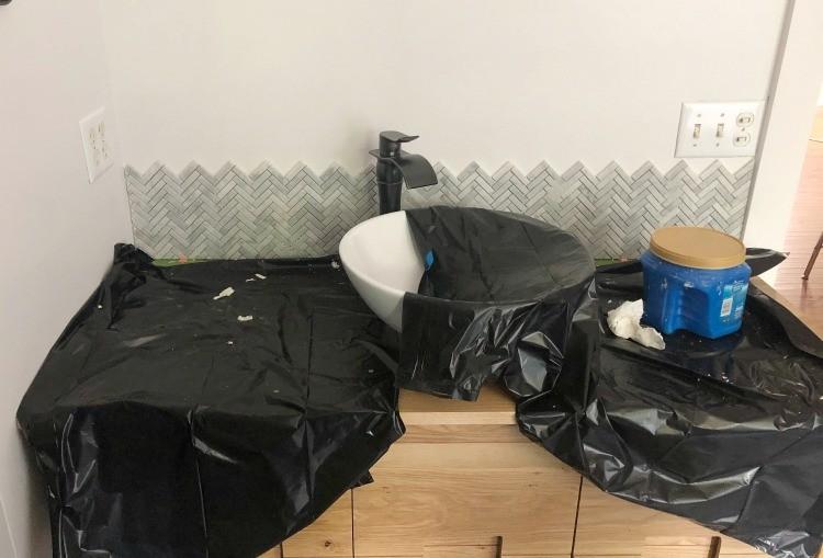 Backsplash installed over vanity top