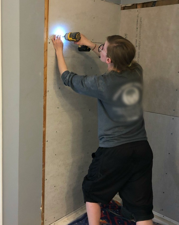 Shara installing cement board into shower walls in bathroom remodel