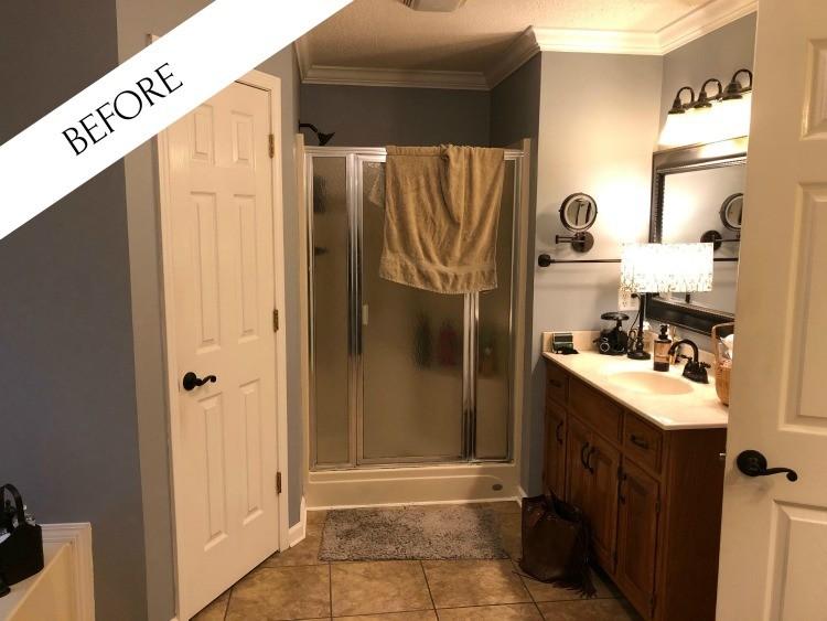 Master Bathroom before--blue walls, dark oak vanity and dark mirror and tan floors