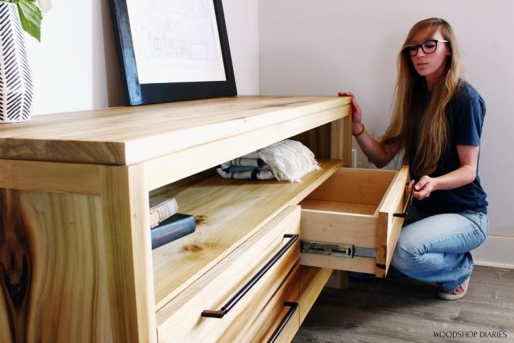 Shara Pulling drawer out of DIY modern dresser to look inside