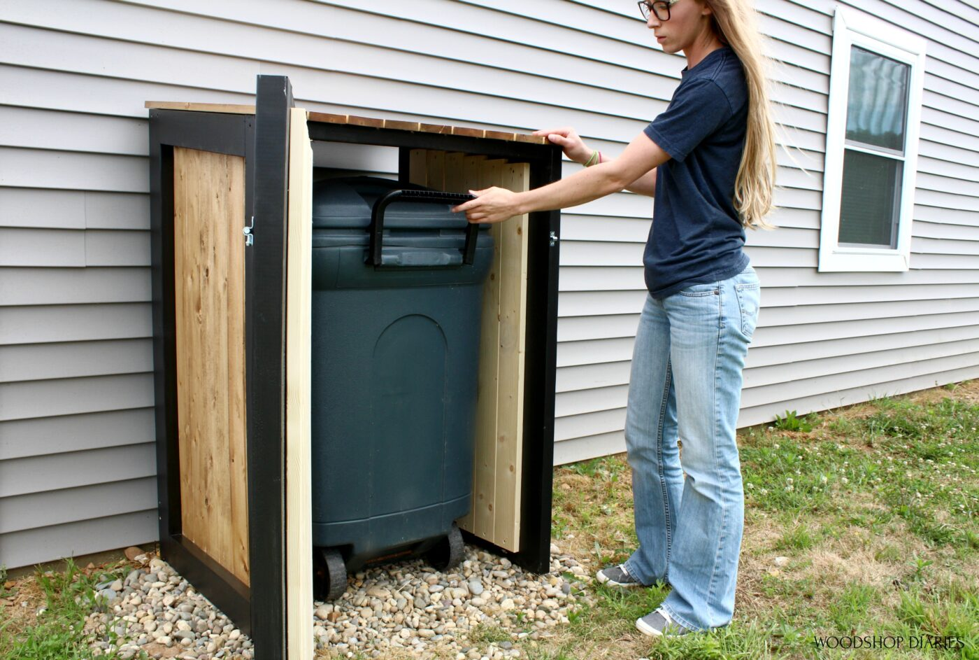 Shara Woodshop Diaries pulling trash can out of trash can cover with door open