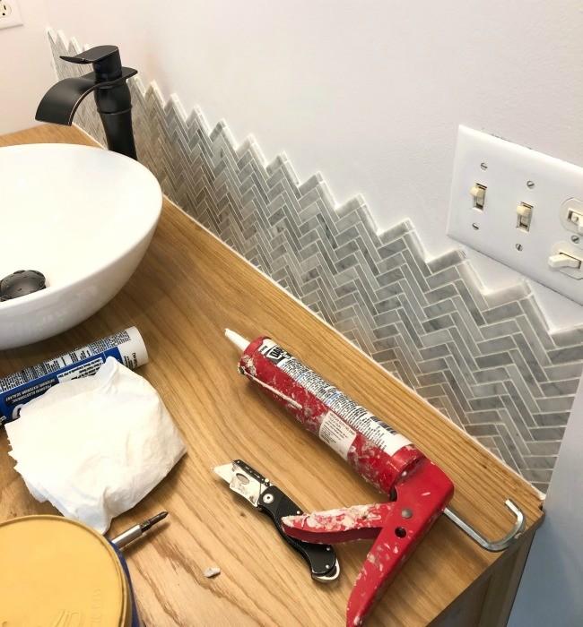 Backsplash installed, grouted, and caulked above vanity