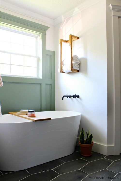 Free standing bathtub in bathroom nook with green feature wall and towel rack