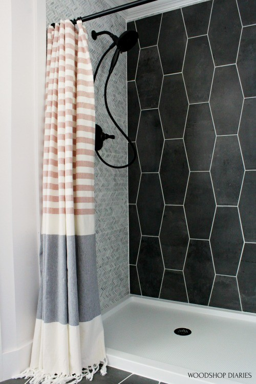 Copper and grey CB2 shower curtain against light and dark grey shower walls and white shower pan