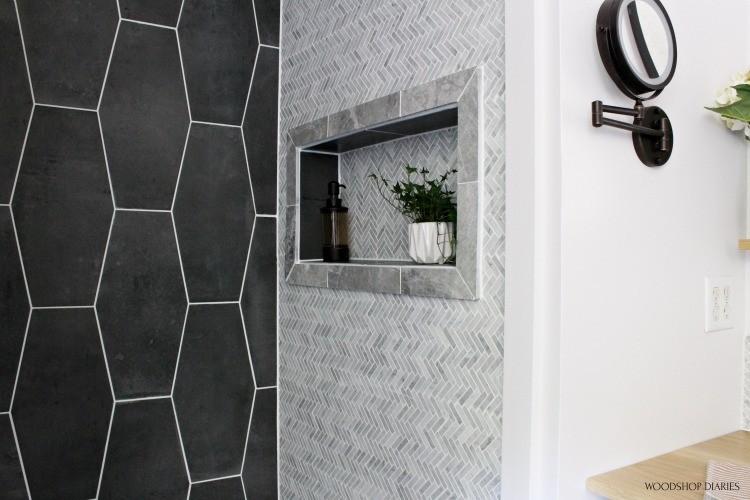 Up close master bathroom shower tile niche with grey framed trim