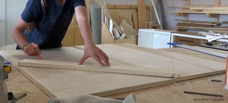 Shara drawing diagonal lines on door pieces before cutting