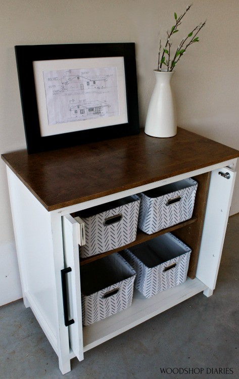 Pocket door cabinet with doors open slid into the cabinet and storage baskets on shelves