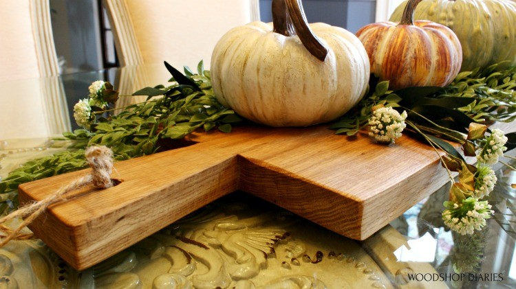 Close up of handle on DIY serving board decorated with pumpkins as a fall centerpiece idea