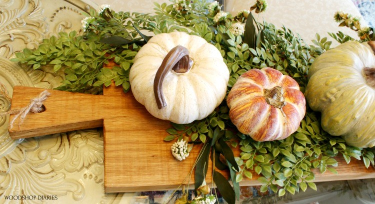 top end of serving board decorated with pumpkins and greenery