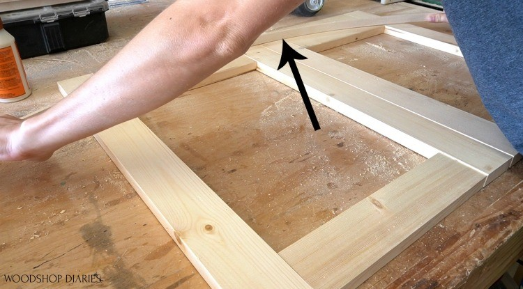 Holding scrap piece to trace out bow to make arched cabinet doors