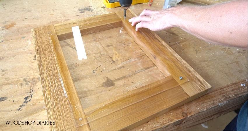 Screwing plexiglass panel to donation box door frame